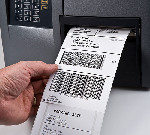 A hand pulling integrated shipping labels out of a printer.