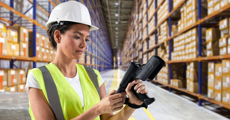 A woman in a distribution center reviewing an item on her scanner.