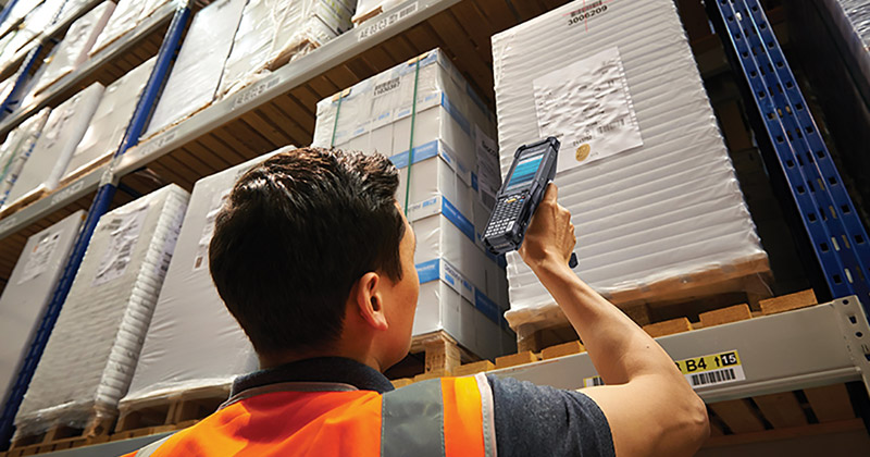 A man in a warehouse scanning a label with the Zebra MC9300 mobile computer.