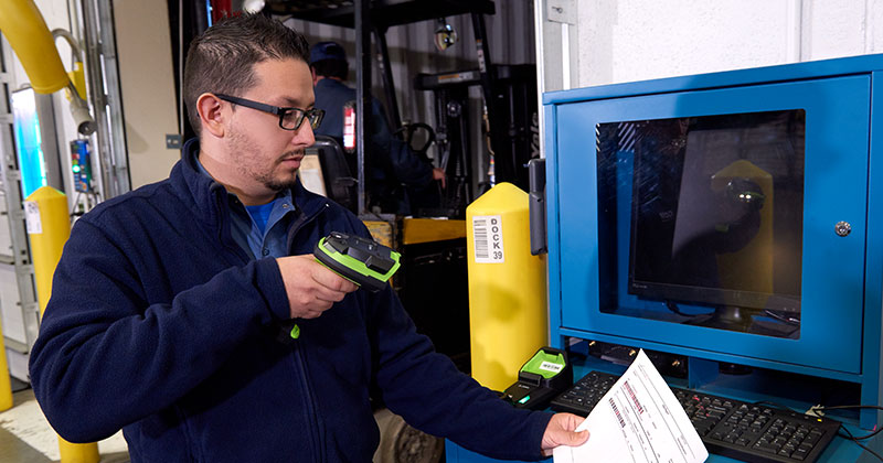 A warehouse worker is scanning a paper document with a Zebra ultra-rugged barcode scanner.